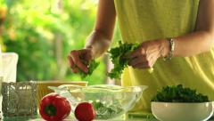 Woman hands picking salad leaves into glass bowl in kitchen HD Stock Footage