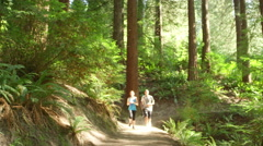 Man and woman stop to rest on a forest path while jogging Stock Footage
