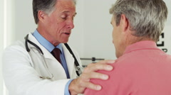 Senior doctor talking to elderly patient with hand on shoulder - stock footage