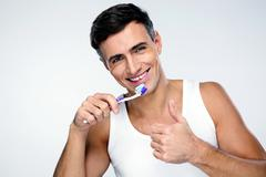 Happy man brushing his teeth over gray background Kuvituskuvat