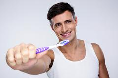 portrait of a smiling man holding toothbrush on gray background - stock photo