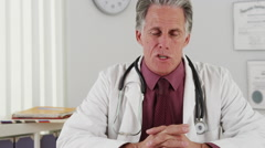Senior doctor talking to camera Stock Footage