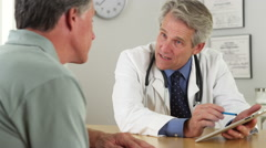 Mature doctor talking with patient and tablet in office Stock Footage