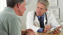 Senior doctor talking with patient and tablet in office Stock Footage