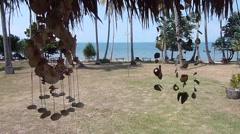 Sea shell wind chimes with shore and sea on tropical paradise island Stock Footage