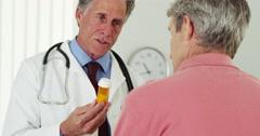 Senior doctor talking to elderly patient about prescription Stock Footage