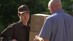 Delivery man delivering packages to customer, slow motion Stock Footage