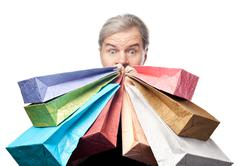 surprised mature man holding shopping bags near face isolated on white backgr - stock photo