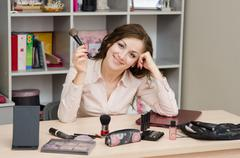 happy girl in the office with cosmetics - stock photo