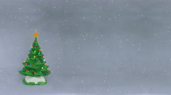 Snow falling on artificial Christmas tree Stock Footage