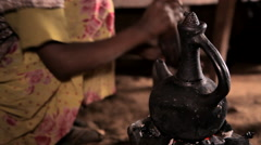 Traditional Ethiopian clay coffee pot on the boil, and a woman in the background - stock footage