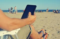 young man using a tablet on the beach - stock photo