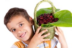 young happy boy holding cherry basket - stock photo