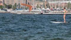 Woman in bikin paddle boards by shore Stock Footage