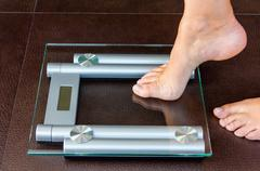 Closeup of woman foot uploading to bathroom scale Stock Photos