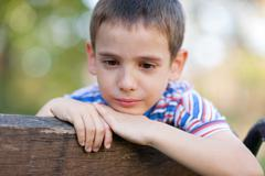 orphan, unhappy boy sitting on a park bench and crying - stock photo