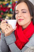 Young smiling women in christmas night drinking hot tea Stock Photos
