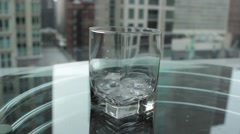Pouring Water into a Clear Glass Tumbler of Ice on a Reflective Glass Table Stock Footage