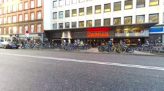 Walking towards the cinema center where lots of bicycles are parked in front - stock footage