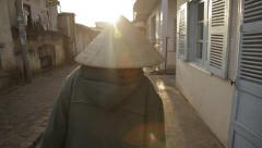 An elderly Vietnamese woman is walking in the poor quarter with bags of things. Stock Footage