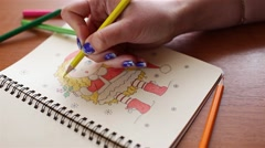 Artist's hand draws a picture of blonde girl Stock Footage