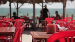 Cafe on the beach: red plastic chairs and wooden tables. Stock Footage