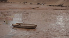 Old boat and remains of human activity are on the bottom of the dried up lake. Arkistovideo