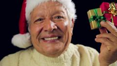 Senior Santa Claus Pointing at Red And Golden Gift - stock footage