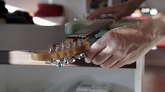 Person changing strings on electric guitar Stock Footage