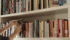 Choose  a book from bookshelf - stock footage
