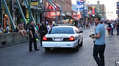 Patrol Car Passes Down Street and Policemen Follow on Foot - stock footage