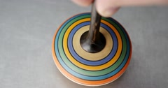 Close up shot of a spinning top moving on a silver surface Stock Footage