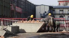 Workers collecting bricks at a construction site in Beijing Stock Footage