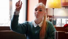 Young woman asking for waiter in cafe Stock Footage