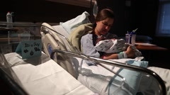 Stock Video Footage of woman holding newborn baby in hospital bed