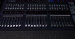 A man pulling up and down knobs on an audio mixer Stock Footage