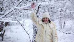 Young woman shake off snow from the branch Stock Footage