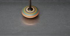 A spinning top moving on a silver surface Stock Footage