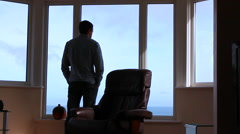 Man Standing At Window Looking At Ocean View Stock Footage