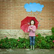 Girl (4-5) with spotty red umbrella pretending to be hiding from rain - stock photo