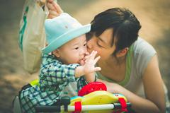 Mother kissing son (6-11 months) - stock photo