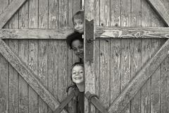 Three children looking out from behind door - stock photo
