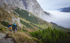 Austria, Salzburg, Two mountain bike riders descending into valley Stock Photos