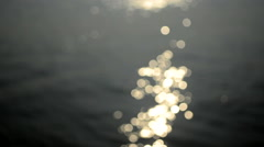 Wide shot of De-focussed  ripples and reflection over water Stock Footage