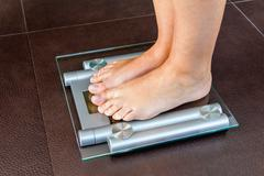 Closeup of woman feet standing on bathroom scale Stock Photos