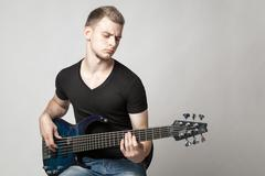 young male musician playing a six-string bass guitar isolated on light backgr - stock photo