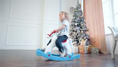 Boy sit on toy horse for rocking Stock Footage