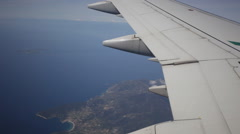 Plane flies by over the sea and the land, in a shot a plane wing Stock Footage