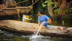 Tonle sap lake, cambodia - circa dec 2013: cambodian boatman cruises down the Stock Footage