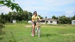 Thai women riding bicycle in the garden Stock Footage